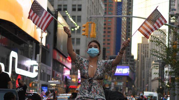 Девушка на одной из улиц в Нью-Йорке после новостей о победе на выборах президента США кандидата от Демократической партии Джозефа Байдена