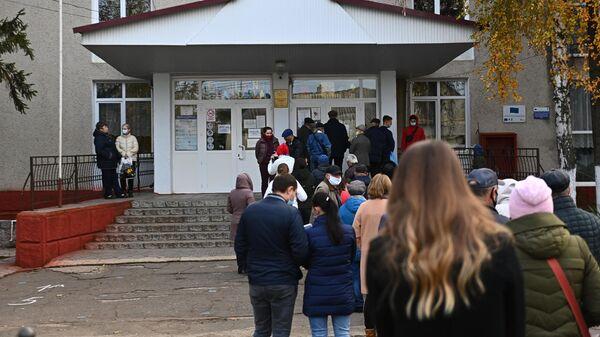 Люди стоят в очереди на избирательный участок в поселке Варница во время второго тура на выборах президента Молдавии