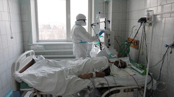 Медицинский работник и пациент в отделении интенсивной терапии ковид-госпиталя в Новоалтайске