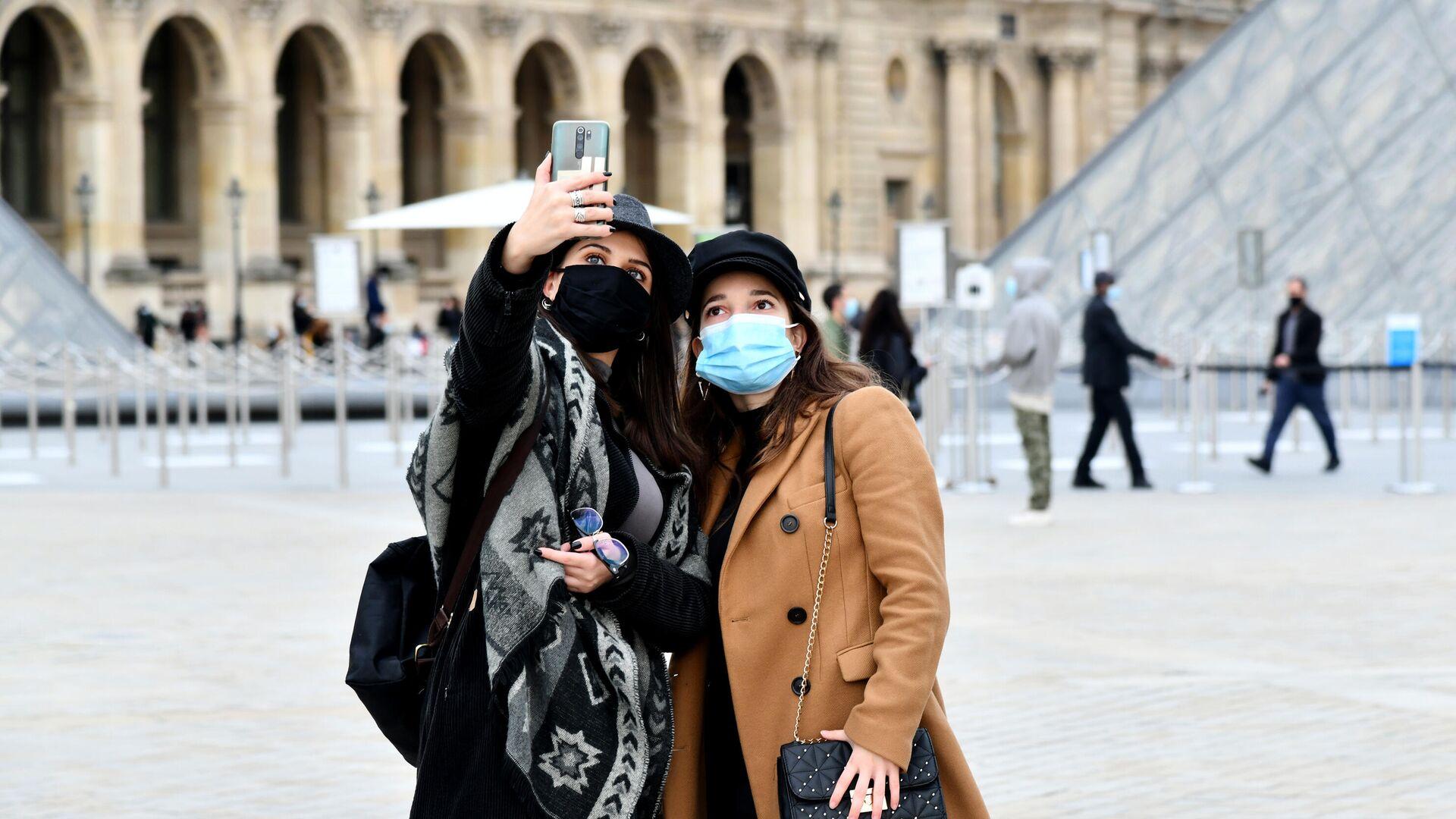 Девушки в масках фотографируются на площади у входа в музей Лувр в Париже - РИА Новости, 1920, 13.03.2021