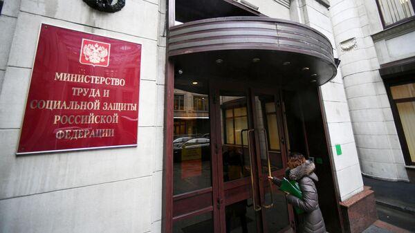 Женщина заходит в здание Министерства труда и социальной защиты Российской Федерации в Москве