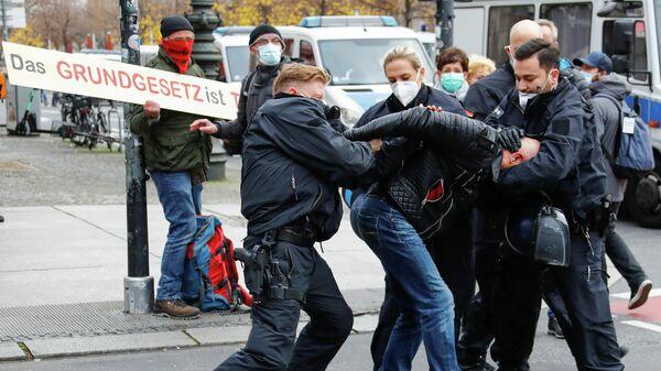 Полицейские задерживают участника протестов у здания бундестага в Берлине