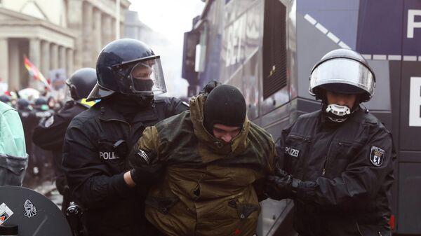 Полицейские задерживают участника протестов в Берлине