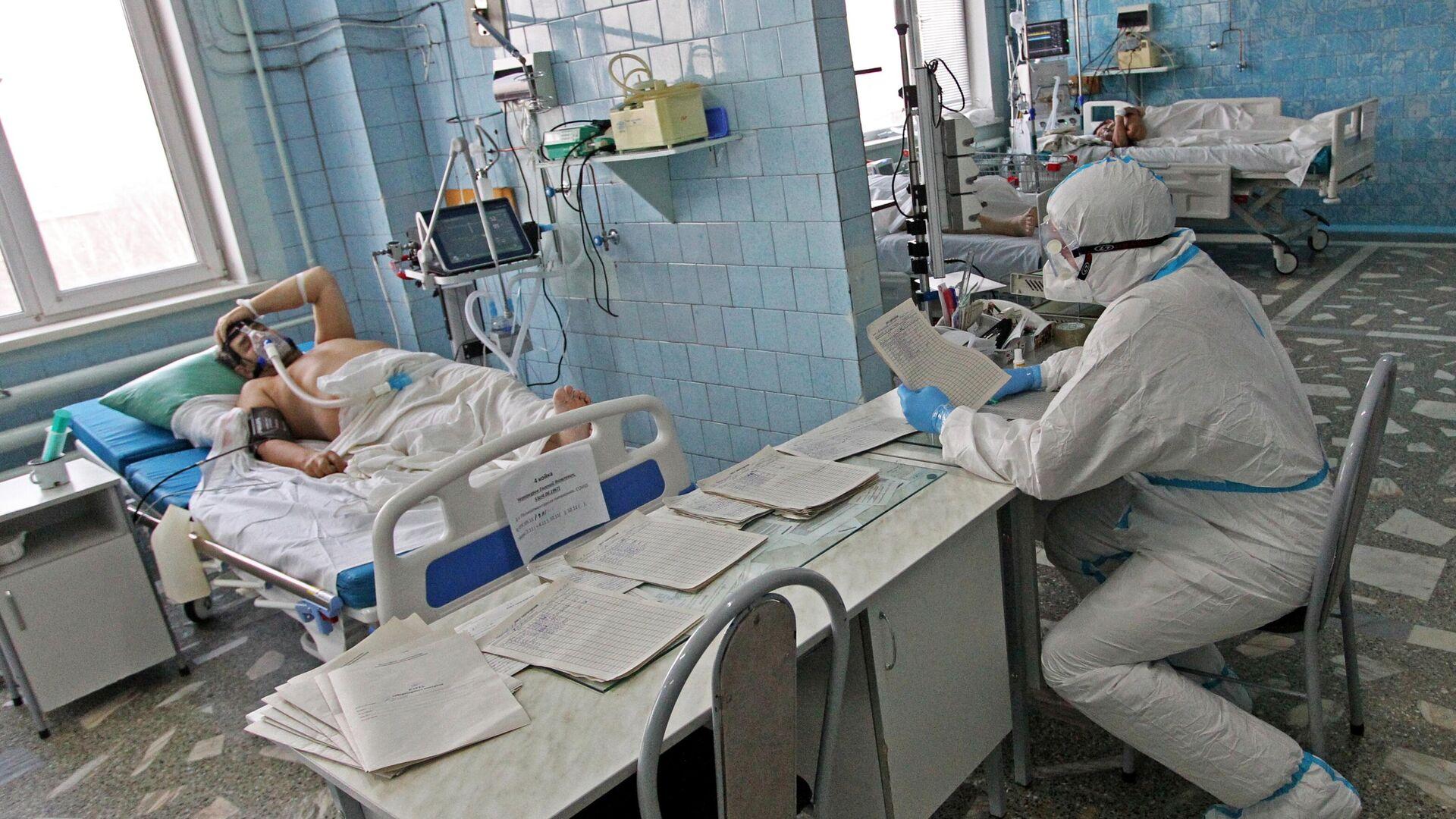 Медицинский работник и пациент в отделении интенсивной терапии ковид-госпиталя в городе Новоалтайске - РИА Новости, 1920, 19.11.2020