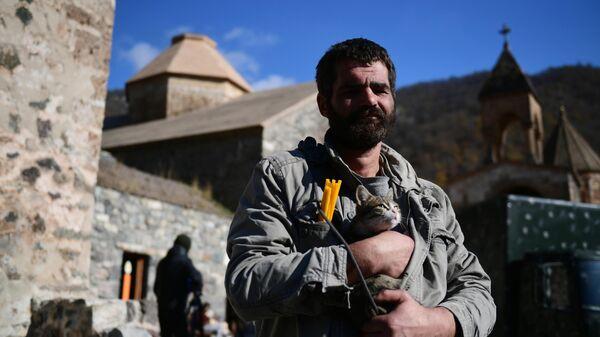 Мужчина держит на руках кота возле храма в монастыре Дадиванк в Нагорном Карабахе