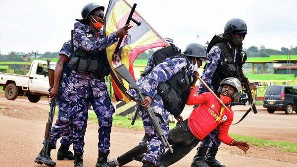 Полицейские и участник протестов в Уганде