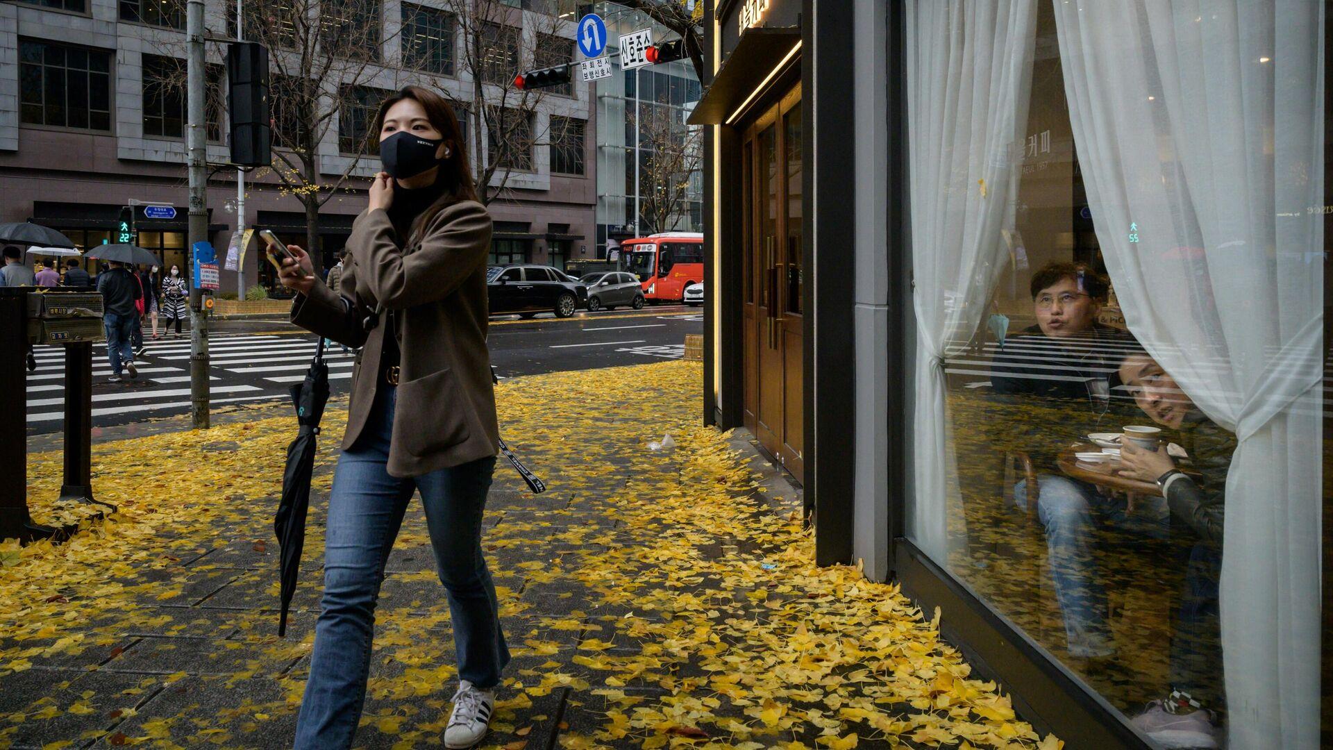 Женщина в маске  на улице в Сеуле, который готовится к третьей волне коронавируса - РИА Новости, 1920, 20.11.2020