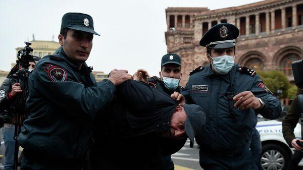 Сотрудники правоохранительных органов задерживают участника акции протеста в Ереване