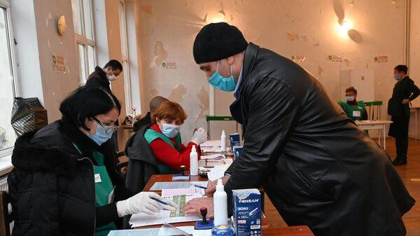 Мужчина голосует во время второго тура парламентских выборов на избирательном участке в Тбилиси