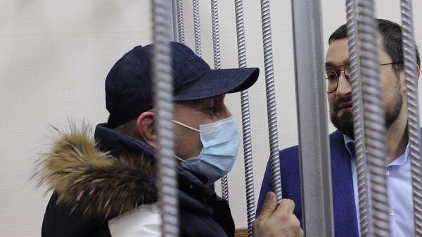 Начальник отдела МВД России по Кизлярскому району Республики Дагестан полковник полиции Гази Исаев разговаривает со своим адвокатом в Басманном суде Москвы