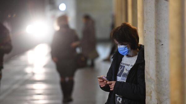 Девушка в защитной маске на одной из станция Московского метрополитена