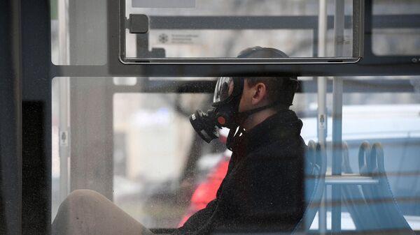 Мужчина в защитной маске с респиратором в общественном транспорте в Москве