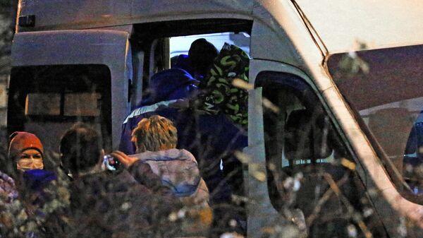 Сотрудник скорой помощи заносит в автомобиль одного из шестерых детей, освобожденных после захвата в городе Колпино
