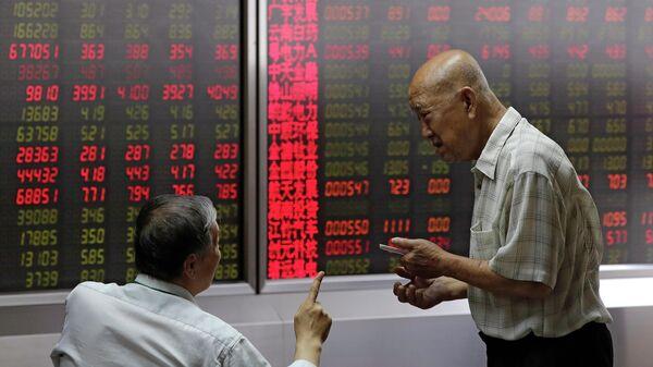 Люди следят за ценами на акции в брокерской конторе в Пекине