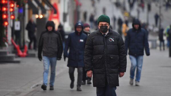 Прохожие в защитных масках на улице в Москве