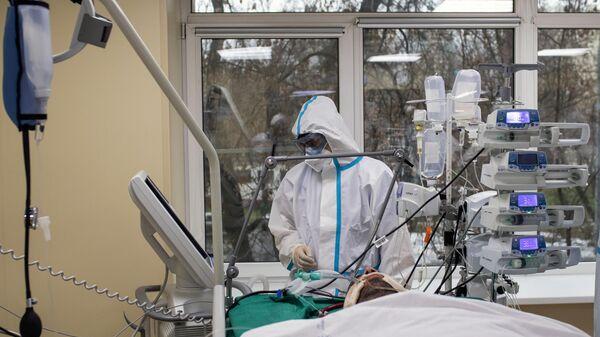 Медицинский работник и пациент в приемном отделении госпиталя COVID-19 в городской клинической больнице № 52 в Москве