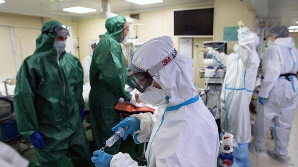 Медицинские работники и пациент в приемном отделении госпиталя COVID-19 в городской клинической больнице № 52 в Москве
