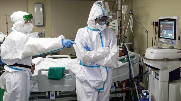 Медицинские работнике и пациент в отделении реанимации и интенсивной терапии в госпитале COVID-19 в городской клинической больнице № 52 в Москве