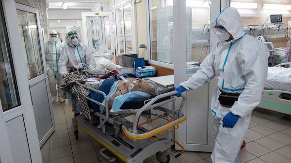 Медицинские работники доставляют пациента в отделение реанимации и интенсивной терапии в госпитале COVID-19 в городской клинической больнице № 52 в Москве