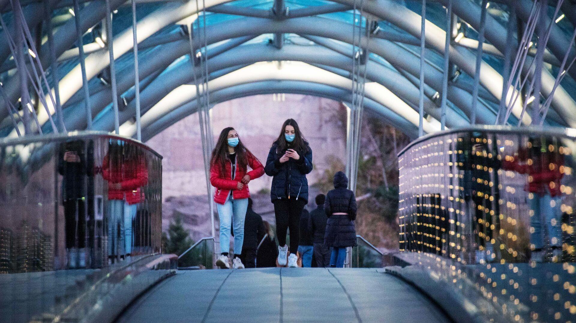 Девушки в защитных масках на одной из улиц в Тбилиси - РИА Новости, 1920, 01.12.2020