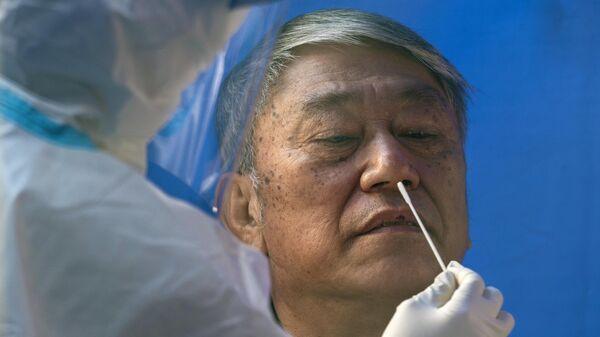 Мужчина проходит тестирование на коронавирус в общественном центре тестирования в Гонконге