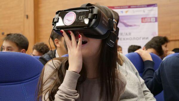 Киргизская школьница смотрит на космос через VR-очки в рамках Дней виртуальной и дополненной реальности в Бишкеке