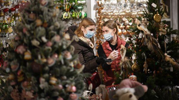 Продажа елочных игрушек и новогодних украшений на новогоднем базаре в ЦУМе в Москве