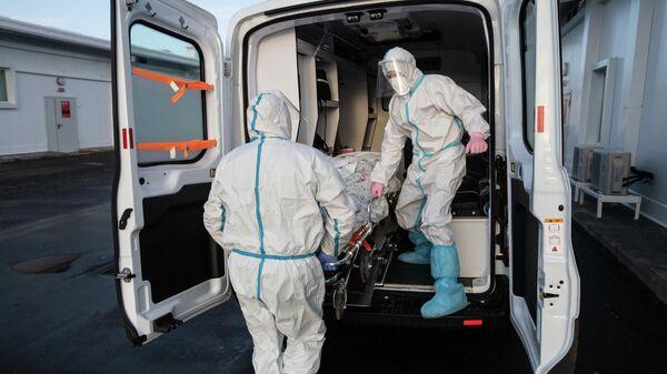 Медицинские работники во время транспортировки пациентки по территории больницы в отделении реанимации и интенсивной терапии в госпитале для больных COVID-19