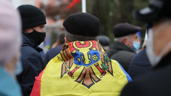 Флаг Молдавии на спине участника акции сторонников избранного президента Молдавии Майи Санду у здания парламента в Кишиневе
