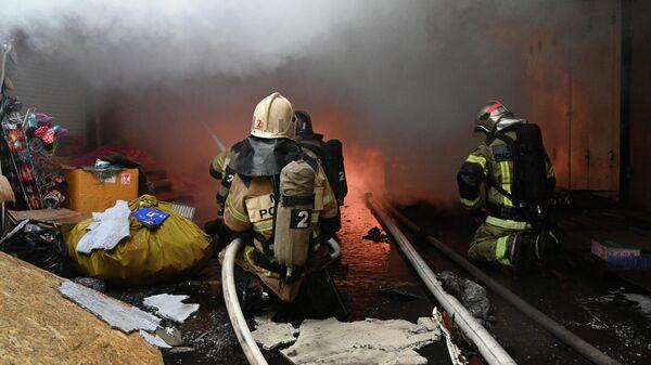 Сотрудники пожарной службы МЧС РФ во время тушения пожара в павильоне с пиротехникой в Ростове-на-Дону