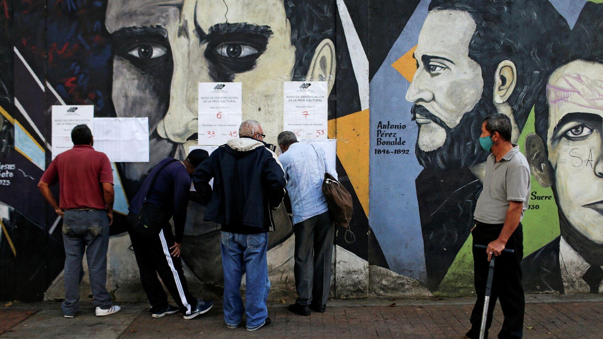 Люди проверяют списки возле избирательного участка во время парламентских выборов в Каракасе, Венесуэла - РИА Новости, 1920, 06.12.2020