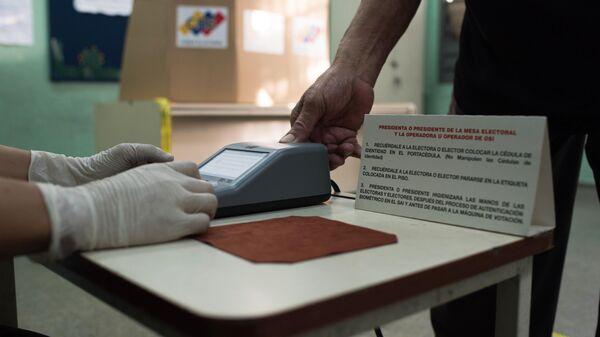 Проверка личности избирателя на избирательном участке во время голосования на выборах в Нацассамблею в Венесуэле
