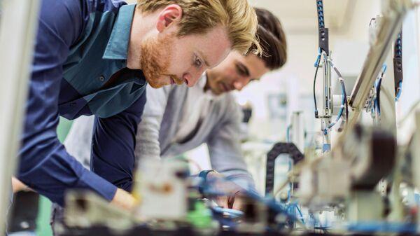 Инженеры во время работы над электронными компонентами микросхемы