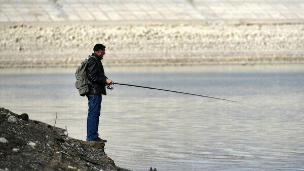 Человек ловит рыбу на берегу Аянского водохранилища в Крыму