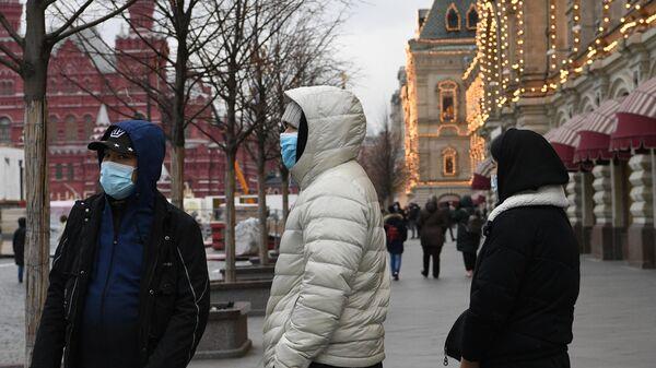 Молодые люди в защитных масках на Красной площади в Москве
