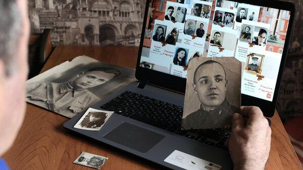 Мужчина смотрит онлайн-трансляцию акции Бессмертный полк