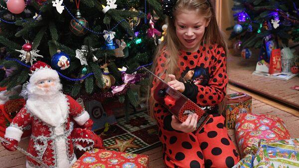 Девочка Маша получает подарки во время празднования Нового года в Москве