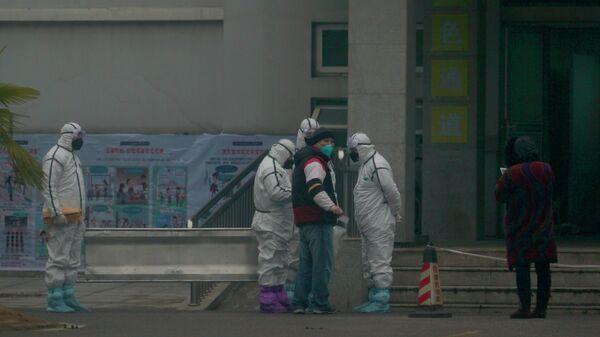 Медики в защитных костюмах возле медицинского центра, где проходят лечение больных коронавирусом, в Ухане