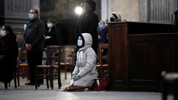Люди во время воскресной мессы в церкви Сен-Сюльпис в Париже