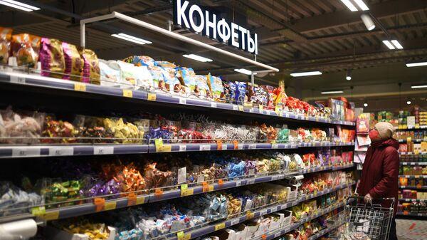 Женщина выбирает конфеты в одном из магазинов сети Пятерочка в Москве
