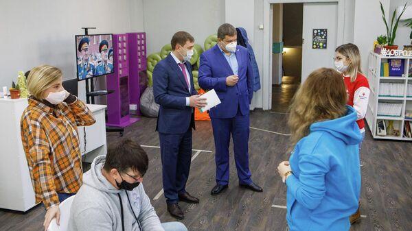Председатель Воронежской областной думы Владимир Нетёсов передает волонтерам оборудование для колл-центра, который принимает звонки от нуждающихся в помощи жителей региона