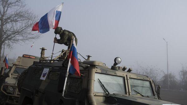 Российский миротворец устанавливает флаг на бронеавтомобиле на блокпосту №6 на въезде в город Шуша на дороге из Степанакерта в Лачин