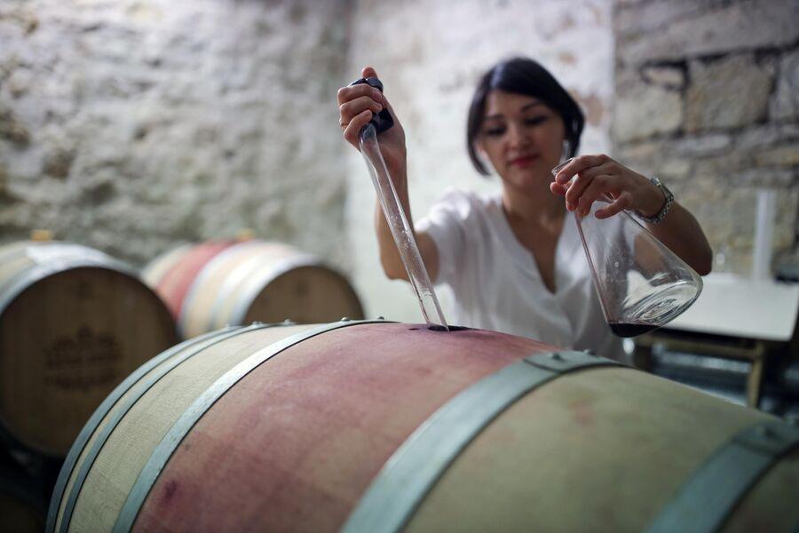 Технолог берет пробу из бочки в коньячном отделении на заводе Русского винного дома Абрау-Дюрсо в Краснодарском крае