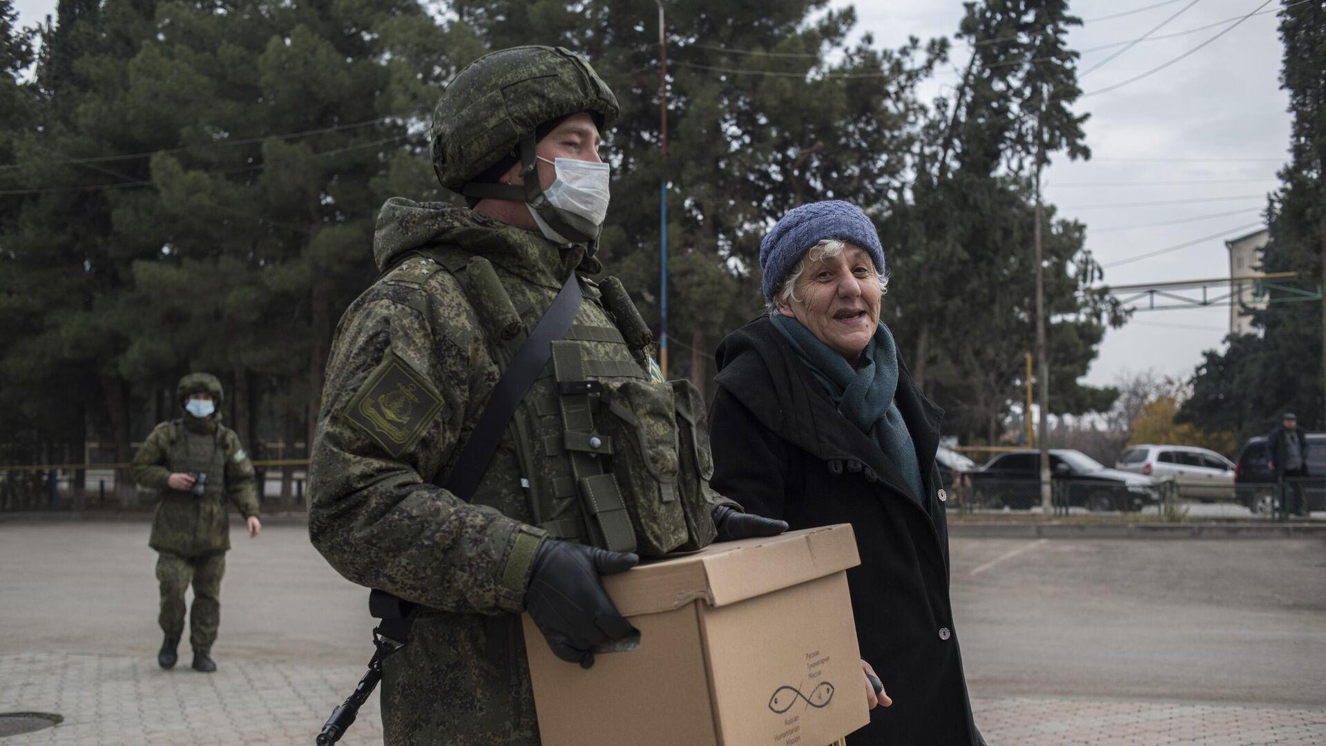Военнослужащий российского центра по примирению враждующих сторон раздает гуманитарную помощь жителям города Мартакерт в Нагорном Карабахе - РИА Новости, 1920, 24.12.2020