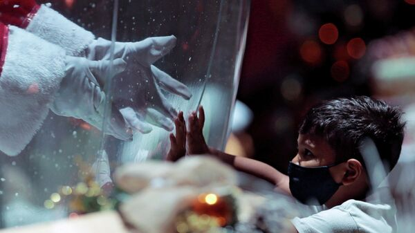 Мужчина в костюме Санта-Клауса внутри пластикового пузыря, приветствует ребенка в торговом центре в Бразилиа, Бразилия