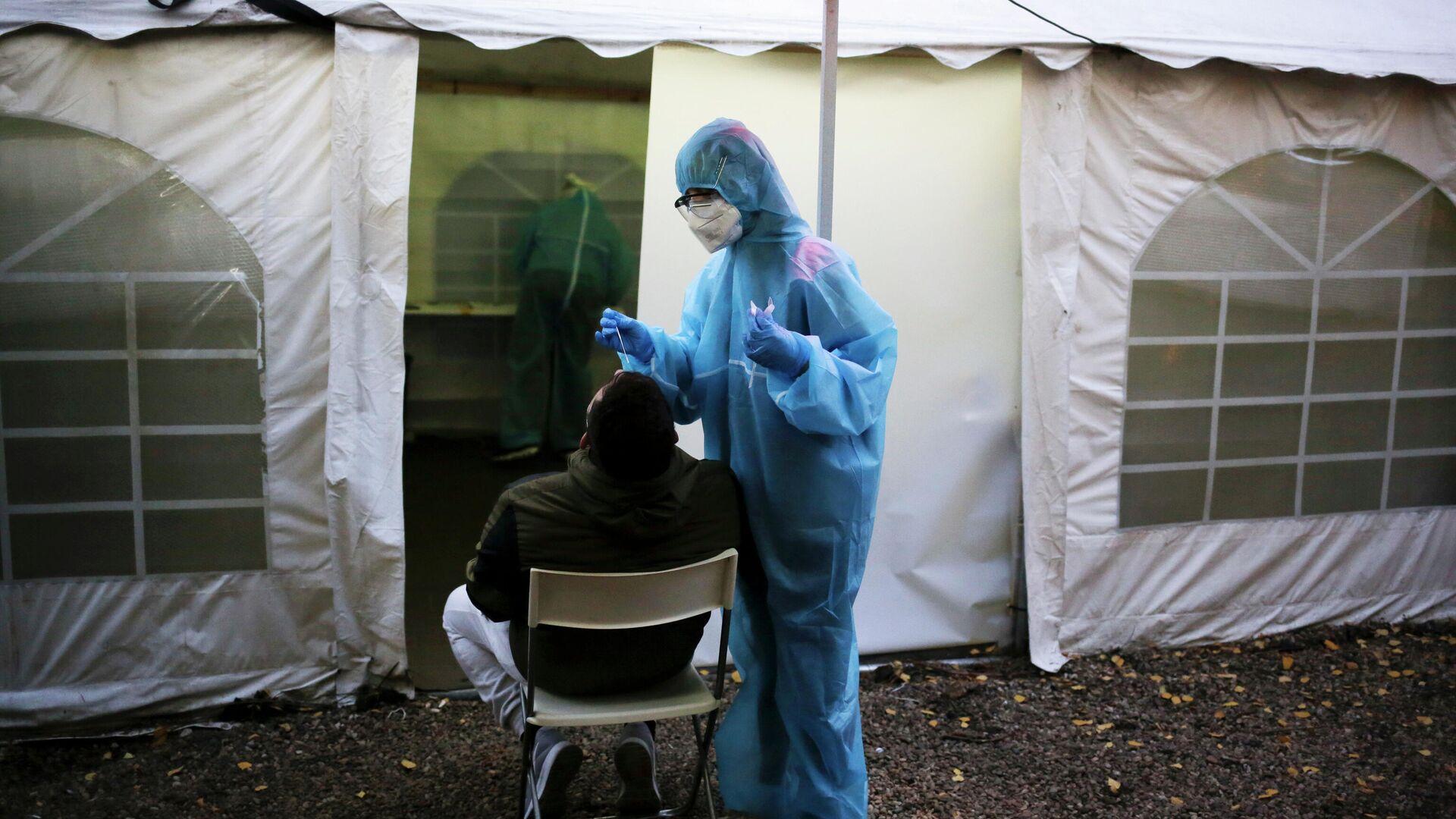 Медик в защитном костюму берет мазок у пациента во время тестирования на SARS CoV-2 в Берлине - РИА Новости, 1920, 22.12.2020