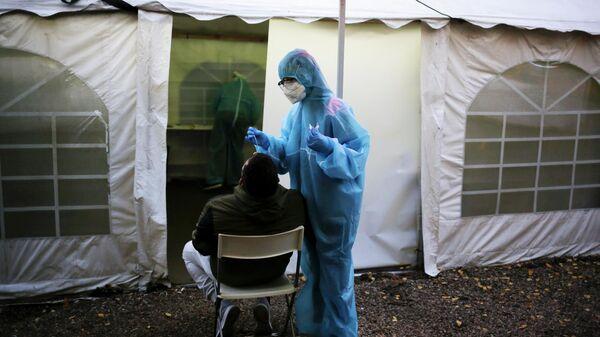 Медик в защитном костюму берет мазок у пациента во время тестирования на SARS CoV-2 в Берлине