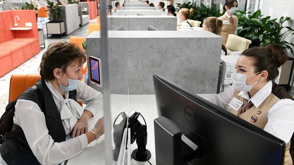 Сотрудники и посетительница нового флагманского центра МФЦ в ТЦ Щелковский в Москве