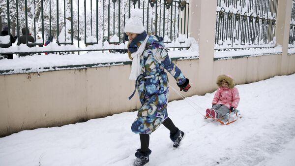 Женщина с ребенком на улице Красных Партизан в Краснодаре после снегопада