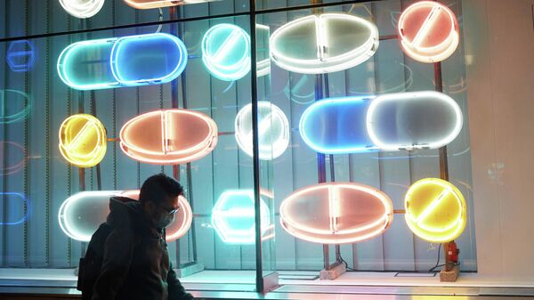 Прохожий на фоне витрины с неоновыми изображениями таблеток в Лондоне